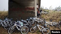 Syrian immigrants traveling by bicycle take shelter from the rain beneath a bridge near the Greek border with Macedonia, June 17, 2015.