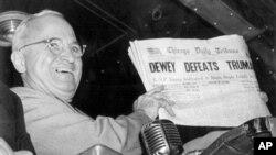 """杜鲁门总统手持一份报纸,报纸上根据早期统计的选举结果错误地宣称""""杜威击败杜鲁门"""""""