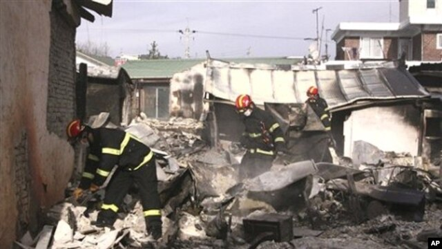 South Korean firefighters inspect destroyed houses on Yeonpyeong island, South Korea, 24 Nov 2010