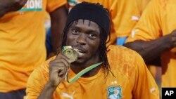Gervinho de la Côte-d'Ivoire mordille sa médaille d'or, célébrant le sacre de l'équipe nationale ivoirienne à la Coupe d'Afrique des nations à Bata, en Guinée équatoriale, 8 février 2015.