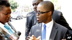 Rev. Jean Louis, right, son of kidnapped Rev. Michel Louis, speaks to the media, in Boston, Massachusetts, July 15, 2012.