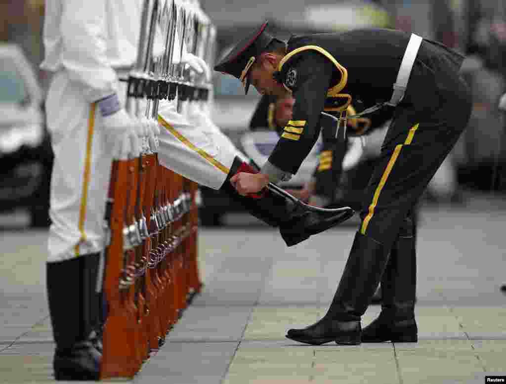 Một thành viên của đội vệ binh danh dự chùi giày cho đồng đội trước buổi lễ nghênh đón Tổng thống Bồ Đào Nha Anibal Cavaco đến thăm bên ngoài Đại lễ đường Nhân dân ở Bắc Kinh.