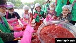 9일 서울 양천구청 주최로 열린 '다문화 여성 및 북한이탈주민 전통 고추장 담그기' 행사에서 참석자들이 새마을 부녀회 회원들의 도움으로 고추장을 담그고 있다.