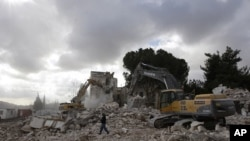A worker walks past excavators during the demolition of the Shepherd Hotel in the Sheikh Jarrah neighbourhood of East Jerusalem, 09 Jan 2011.