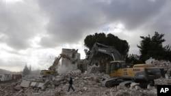 A worker walks past excavators during the demolition of the Shepherd Hotel in the Sheikh Jarrah neighbourhood of East Jerusalem, 09 Jan 2011.