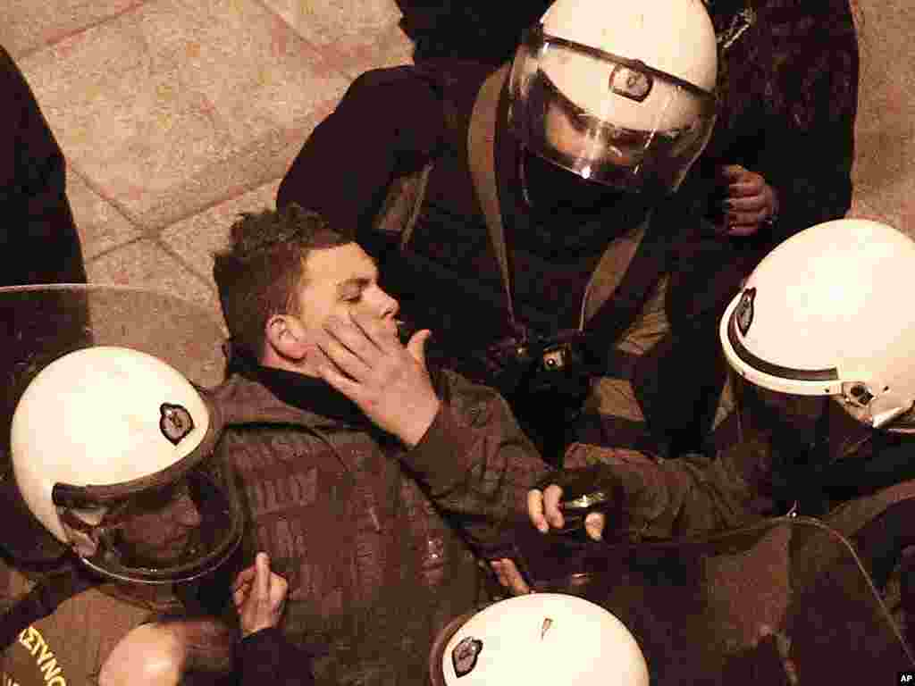 Riot police detain a protester during a small demo at Athens' main Syntagma Square on February 19, 2012. (AP)