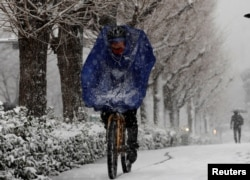 A man rides a bicycle in the heavy snow in Tokyo, Japan, Jan. 22, 2018.