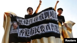 Pro-democracy activists protest on the Golden Bauhinia Square, a gift from China at the 1997 handover, during a protest a day before Chinese President Xi Jinping is due to arrive.