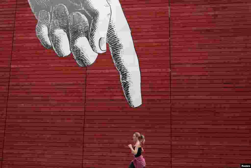 Seorang perempuan berlari melewati karya seni tangan yang besar di sebuah dinding di tengah kota London, Inggris.
