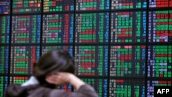 FILE - An investor monitors the stock market at a securities brokerage in Taipei.