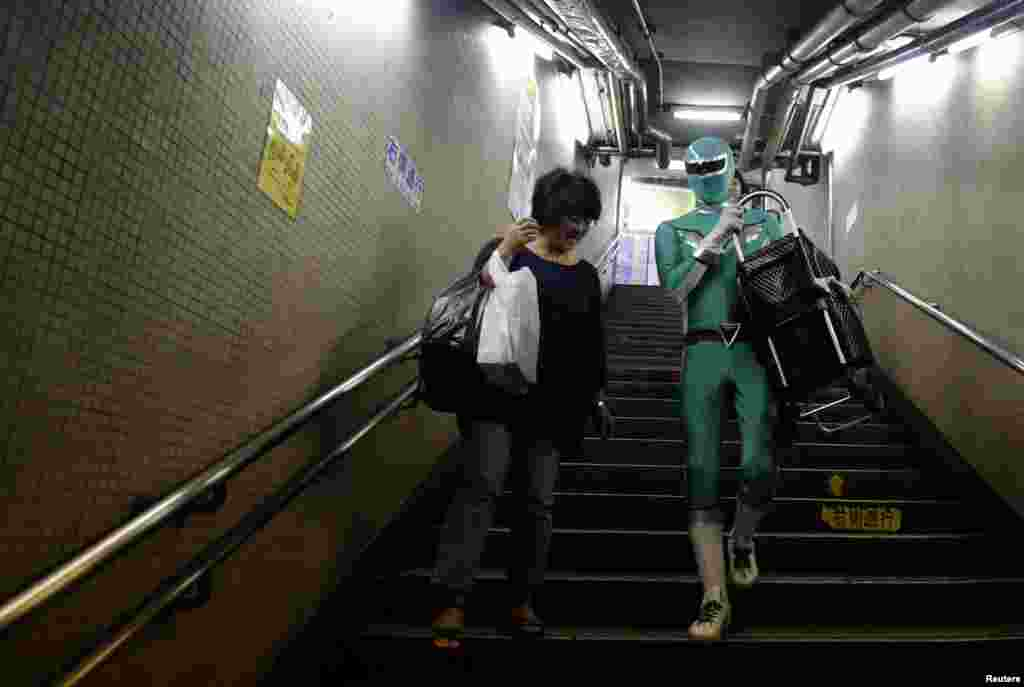 "Tadahiro Kanemasu a.k.a the ""Carry-Your-Pram-Ranger"" carries a woman's shopping cart at the station in Tokyo, Japan. In a green outfit with silver trim and matching mask, a superhero waits by the stairs of a Tokyo subway station, lending his strength to the elderly, passengers lugging heavy packages and mothers with baby strollers."