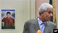 (អតីត) រដ្ឋមន្ត្រីការបរទេសលីប៊ី ម៉ូសា គូសា (Moussa Koussa) អានសេចក្តីថ្លែងការណ៍ដល់អ្នកយកព័ត៌មានបរទេសនៅសណ្ឋាគារមួយនៅទីក្រុងទ្រីប៉ូលី (Tripoli) ប្រទេសលីប៊ី កាលពីថ្ងៃទី១៨ខែមីនាឆ្នាំ២០១១។