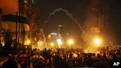 这张于2013年1月26日拍摄的图片显示,在开罗市中心沿着尼罗河岸的一家国际大饭店的前面,安全部队使用催泪瓦斯回击向他们扔石头的示威者