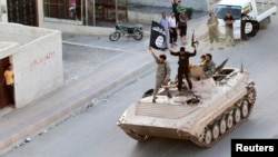 FILE - Militant Islamist fighters hold the Islamic State group's flag while parading in northern Raqqa province, Syria, June 30, 2014. The U.S. Justice Department charged six Bosnian immigrants with aiding terrorists including IS.
