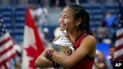 Emma Raducanu, of Britain, hugs the US Open championship trophy after defeating Leylah Fernandez, of Canada, during the women's singles final of the US Open tennis championships, Saturday, Sept. 11, 2021, in New York.
