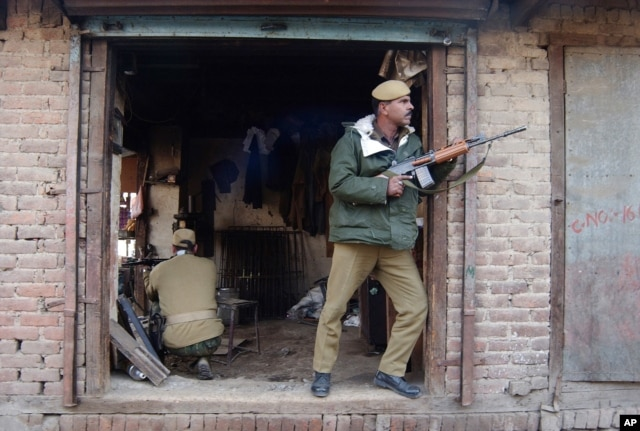 Indian paramilitary soldiers take position in a shop during a gun battle with suspected militants in Srinagar, India, Nov. 23, 2005.