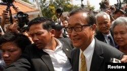 Sam Rainsy (kanan), pemimpin partai oposisi Kamboja CNRP, tiba di pengadilan di Phnom Penh (14/1). (Reuters/Samrang Pring)