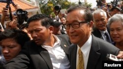 FILE - Sam Rainsy (R), leader of the opposition Cambodia National Rescue Party (CNRP), arrives at the Municipal Court in central Phnom Penh, Jan. 14, 2014.