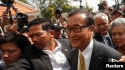 Pemimpin oposisi Kamboja, Sam Rainsy (kanan), tiba di pengadilan kota Phnom Penh (14/1).