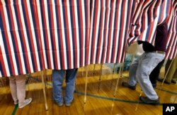 "FILE - A voter enters a booth at a polling place in Exeter, N.H., Nov. 8, 2016. Donald Trump won the presidency, even as he lost the popular vote to Democrat Hillary Clinton. He nonetheless tweeted on Nov. 26 that he won the popular vote. and alleged there was ""serious voter fraud"" in California, New Hampshire and Virginia. There's no evidence to back up those claims."