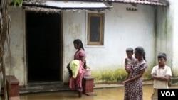 Sebuah keluarga berdiri di depan rumah mereka yang tergenang air di wilayah Batticaloa, di timur ibukota Kolombo (6/2).