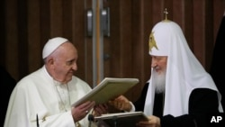 Pope Francis, left, and Russian Orthodox Patriarch Kirill exchange a joint declaration on religious unity at the Jose Marti International airport in Havana, Cuba, Feb. 12, 2016.