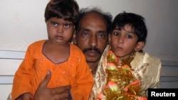 کراچی ایک پولیس اسٹیشن میں سات سالہ دولہا وسیم اور چار سالہ دلہن نیشا، اور ان کا والد اسماعیل۔ پولیس نے انہیں شادی کے موقع پر چھاپہ مار کر گرفتار کیا۔ فائل فوٹو