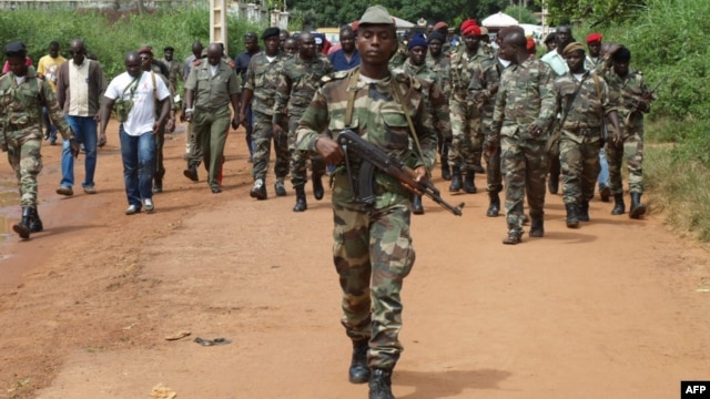Guinea Bissau soldiers walk on October 21, 2012 in a street of Bissau after gunmen raided a Guinea-Bissau army barracks in the capital, sparking a firefight that left at least seven people dead in the latest unrest to blight the chronically unstable count