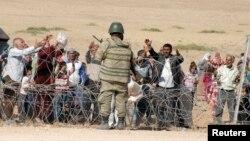 Binh sĩ Thổ Nhĩ Kỳ đứng gác trong khi người Kurd ở Syria chờ đợi để vượt biên vào Thổ Nhĩ Kỳ, gần thị trấn Suruc ở tỉnh Sanliurfa miền đông nam, 19/9/2014.