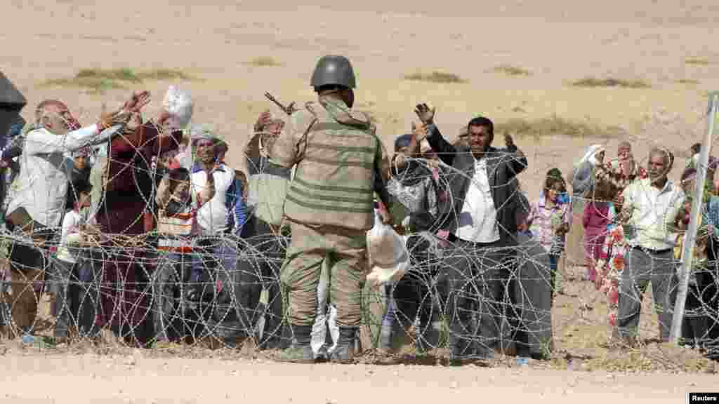 A Turkish soldier stands guard as Syrian Kurds wait behind the border fence to cross into Turkey near the southeastern town of Suruc in Sanliurfa province, Sept. 19, 2014.
