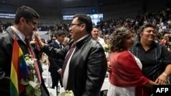 FILE - Same-sex couples Juan Jose Murillo, far left, and Ernesto Alonso Osuna, and Lorena Ramirez, right, with Rosa Isaura Vega take part in a mass wedding ceremony at the Municipal Auditorium in Tijuana, Baja California, Mexico, on Feb. 14, 2020.