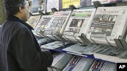 A man views a news stand displaying newspapers, some carrying the story on WikiLeaks' release of classified US State Department documents, in London.