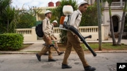 FILE - Government fumigators prepare to spray homes for mosquitoes in Havana, Cuba, Feb. 22, 2016.