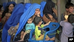 An Afghan woman sits amidst her children as they wait to be repatriated to Afghanistan from a United Nations Humanitarian Commission for Refugees (UNHCR) registration center in Peshawar, Pakistan, Jun 20, 2010 (file photo)