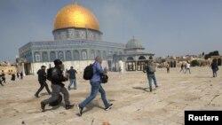 Pripadnik izraelske policije trči za snimateljem tijekom sukoba s Palestincima u kompleksu u kojem se nalazi džamija Al-Aqsa, koja je muslimanima poznata kao Plemenito utočište, a Židovima kao Hramska planina, u starom gradu Jeruzalema, 10. maja 2021. REUTERS / Ammar Awad