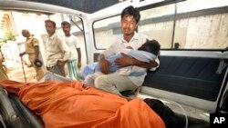 17일 인도 바이하르에서 한 남성이 무료 학교 급식을 먹고 죽은딸을 안고 애통해 하고 있다.