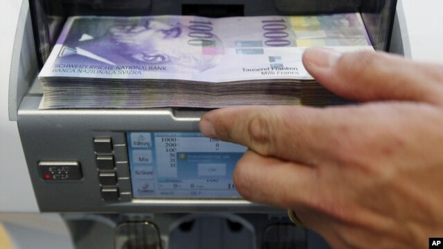 A bank clerk places1000 Swiss franc banknotes in a money counter in a Bank in Bern August 15, 2011. The Swiss franc rose against the euro and the dollar as renewed worries about the euro zone crisis pushed investors towards the safe-haven currency despite
