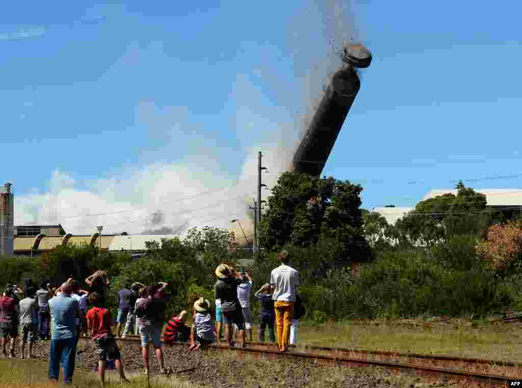 A 200-meter-high chimney, built from about 7,000 tons of concrete, bricks and steel, is brought down in a controlled explosion at Port Kembla, south of Sydney, Australia. Nearly 1,000 explosive charges were placed around the copper stack, which broke into at least two pieces just before hitting the ground as thousands of people gathered to watch the explosion.