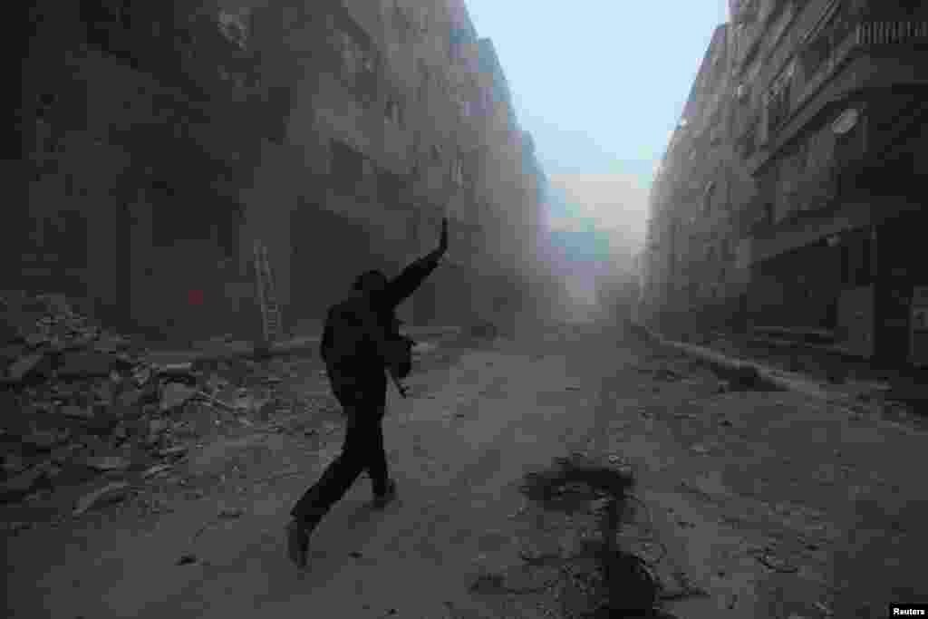 A rebel fighter gestures as he runs across a street in Mleha suburb of Damascus, April 2, 2014.