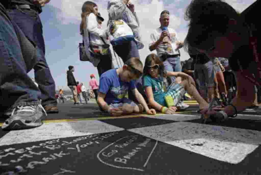 Miles de fanáticos se acercan a escribir sus nombres en el meta antes de que los carros participen de la primera competencia en Daytona.