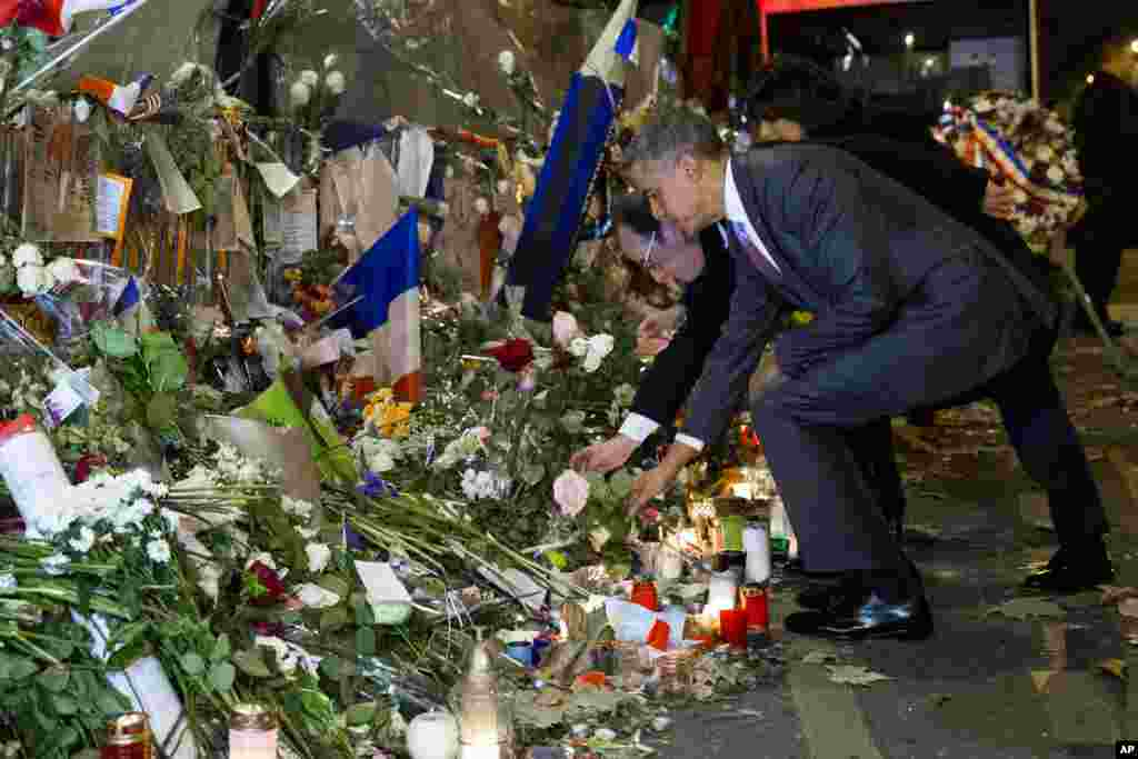 President Barack Obama, right, and French President Francois Hollande place flowers at the Bataclan, site of one of the Paris terrorists attacks, to pay respects after arriving in town for the COP21 climate change conference in Paris.