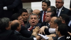 FILE - Ruling Justice and Development Party lawmakers and members of the Republican People's Party skirmish during debate on corruption charges against ministers in the cabinet of then-Prime Minister Recep Tayyip Erdogan in Ankara, Turkey, May 5, 2014.
