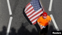 A runner carrying a US flag passes the shadows of spectators during the London Marathon April 21, 2013.