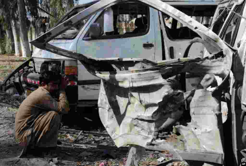 A Pakistani man sits next to his destroyed vehicle at the site of a car blast on the outskirts of Peshawar on February 23, 2012. (AFP photo)