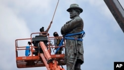 FILE - Workers prepare to take down the statue of former Confederate general Robert E. Lee in New Orleans, May 19, 2017.