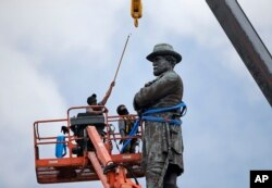 FILE - Workers prepare to take down the statue of former Confederate general Robert E. Lee, which stands more than 100 feet tall, in Lee Circle in New Orleans, May 19, 2017.