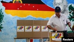 A man casts his ballot in a box during a municipal elections in Caracas, Venezuela, Dec. 8, 2013.