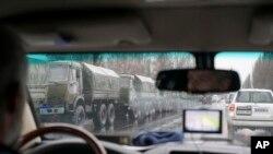 Cette photo prise par la mission de surveillance de l'OSCE dans la ville de Louhansk, dans l'est de l'Ukraine, montre des véhicules blindés et des hommes armés circulant dans le centre-ville, le 21 novembre 2017.