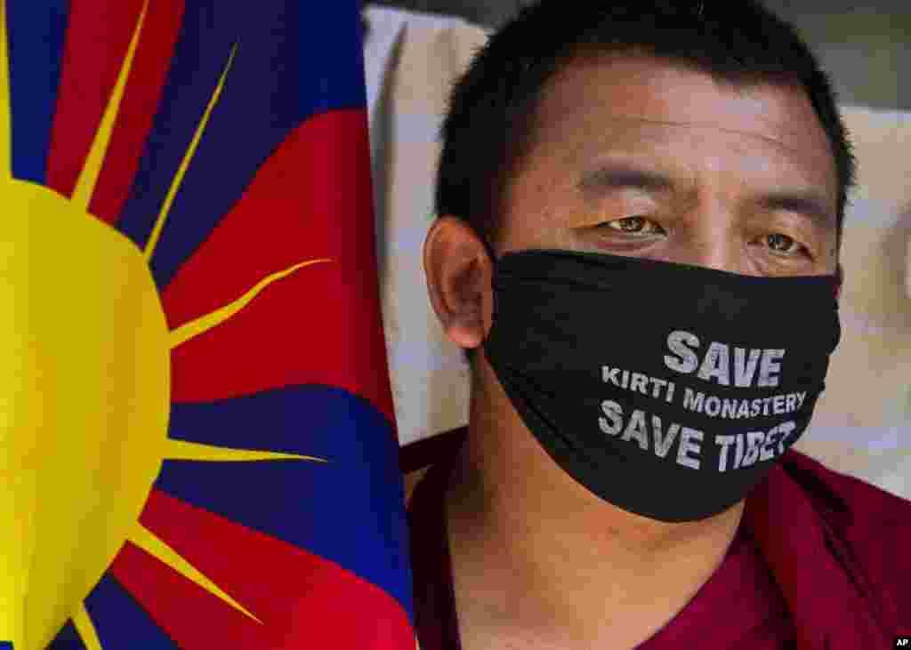 인도 다람살라에서 티베트 국기를 들고 얼굴에 마스크를 착용한체 항의시위를 벌이는 한 남성
