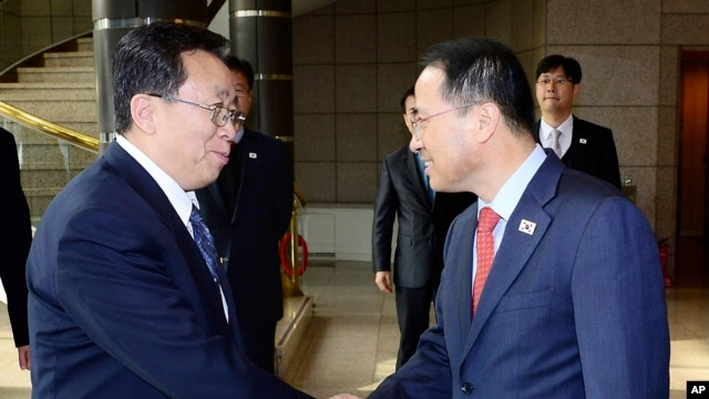 South Korean chief delegate Kim Kyou-hyun, right, shakes hands with his North Korean counterpart Won Tong Yon upon his arrival at the border village of Panumjom, South Korea, Wednesday, Feb. 12, 2014.